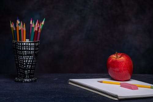 Set of multicolored pencils in cup holder placed on table with eraser on copybook and ripe red apple on black background