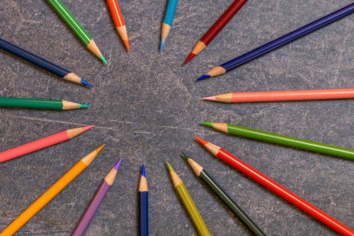 Top view set of multicolored wooden pencils with sharp tips arranged in form of circle on dark table in studio