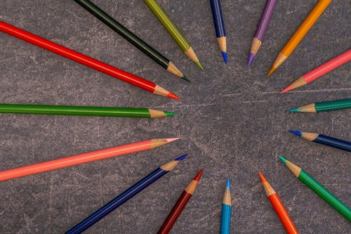 Multicolored pencils arranged on shabby table