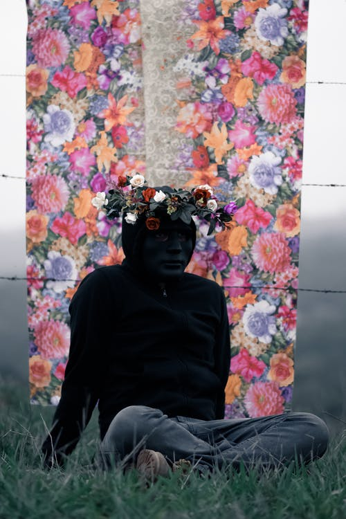 Full body anonymous person in dark casual wear and black incognito mask wearing wreath on head and sitting on grassy meadow against building wall with floral ornament