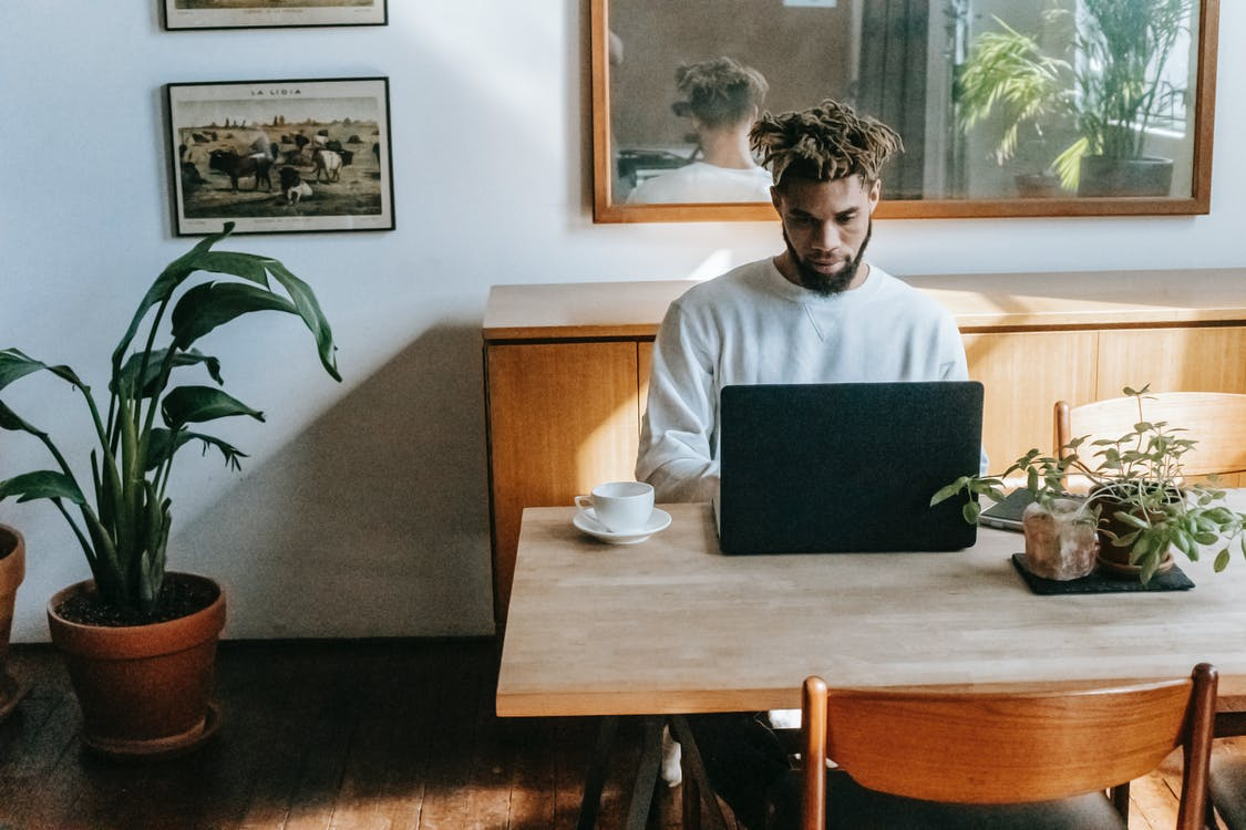 Focused black man browsing laptop at home
