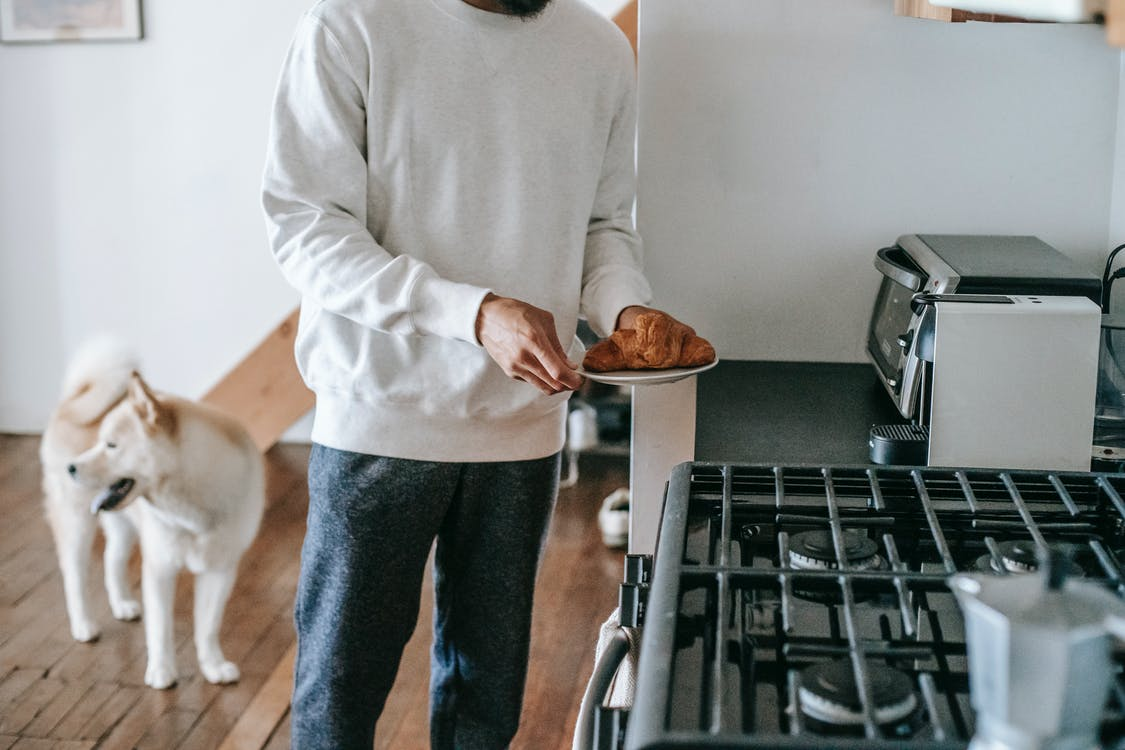 Faceless man with croissant in hand standing in kitchen with cute dog