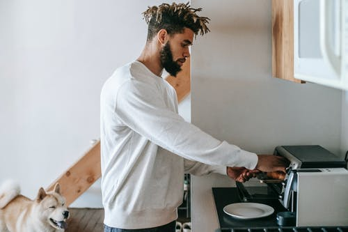 Bearded young black man heating croissant in microwave oven standing near dog