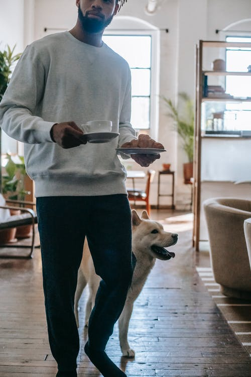Ethnic man standing near dog with coffee cup and plate of pasty in hand