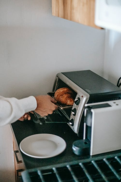 From above of crop anonymous person using microwave oven while heating yummy croissant for breakfast