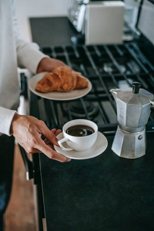 From above of crop unrecognizable person in casual clothes holding plate with fresh croissant and cup of coffee brewed in moka pot before breakfast in kitchen