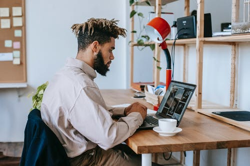 Side view of African American male freelancer in casual outfit sitting at wooden table and working on laptop near cup of coffee and lamp near shelves in light room