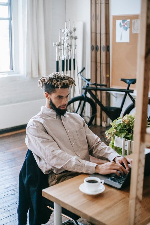 Serious African American male freelancer in casual clothes sitting at wooden table while working on netbook with cup of coffee and bicycle in workplace