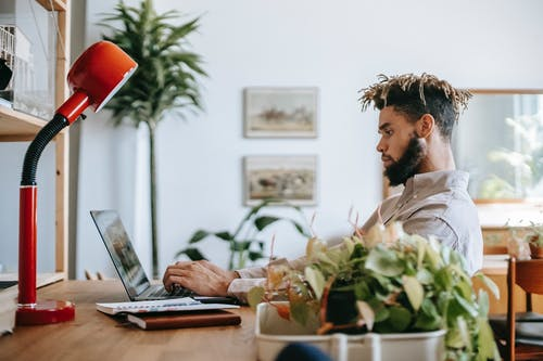 Side view of concentrated black guy in casual outfit sitting at wooden table while working remotely on computer with notepad and lamp in workspace