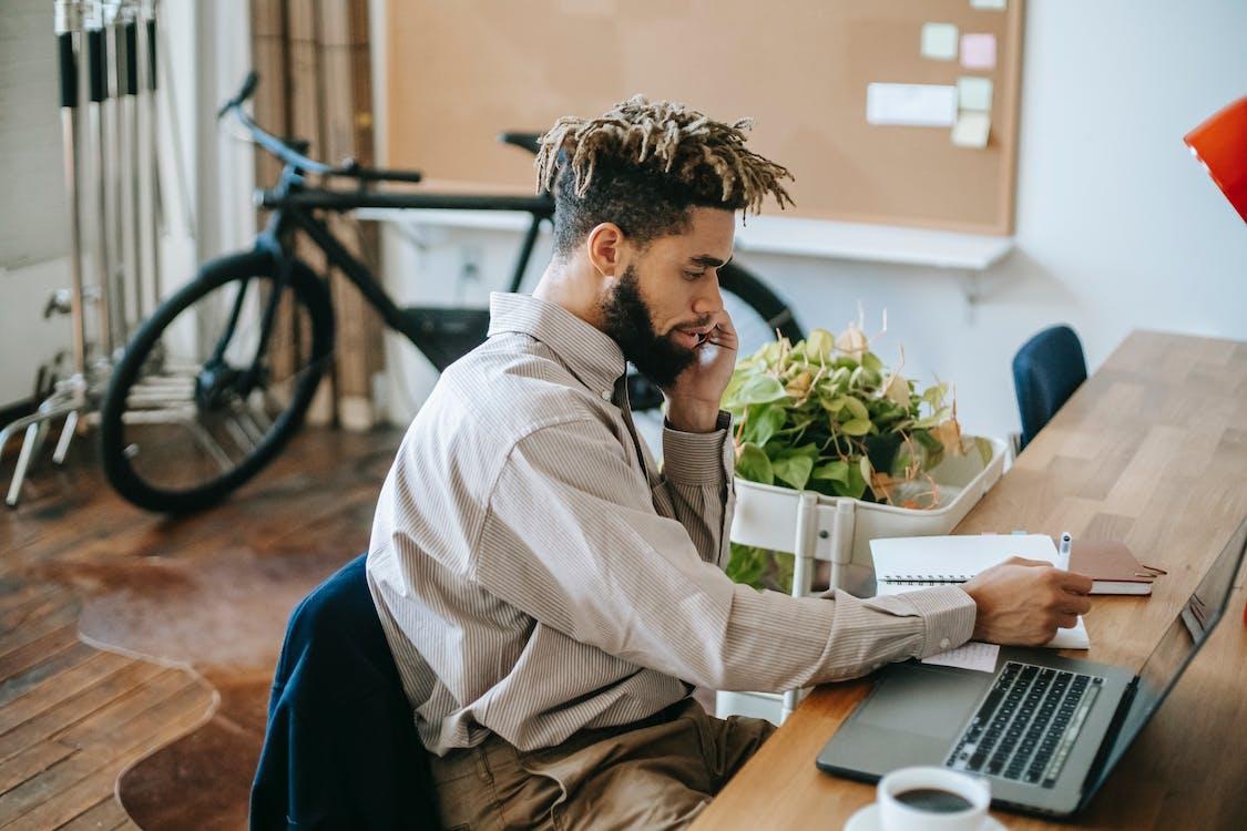 Black man working remotely on laptop in workspace