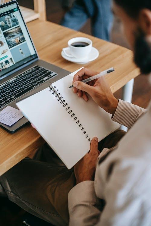 Pessoa Segurando Uma Caneta Escrevendo Em Um Caderno