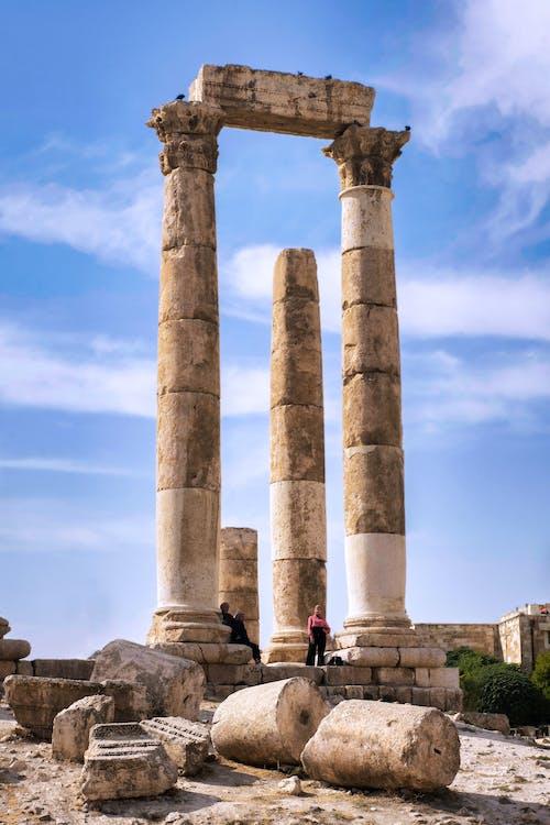 People Walking on Gray Concrete Pillar Under Blue Sky