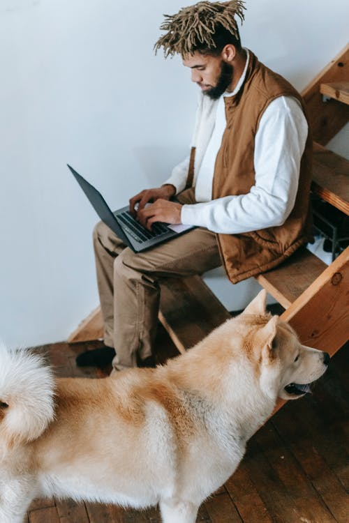 African American guy sitting on stairs with netbook near dog