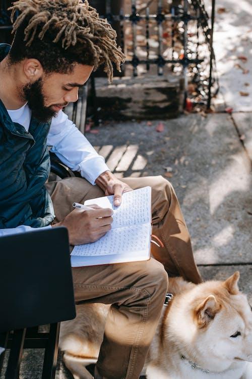 Ethnic man sitting with dog on bench