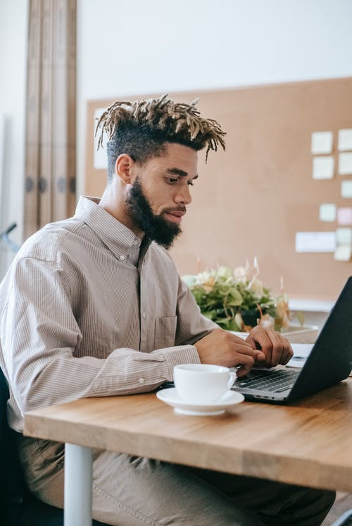 Man In Dress Shirt Sitting At The Table Using Laptop Computer