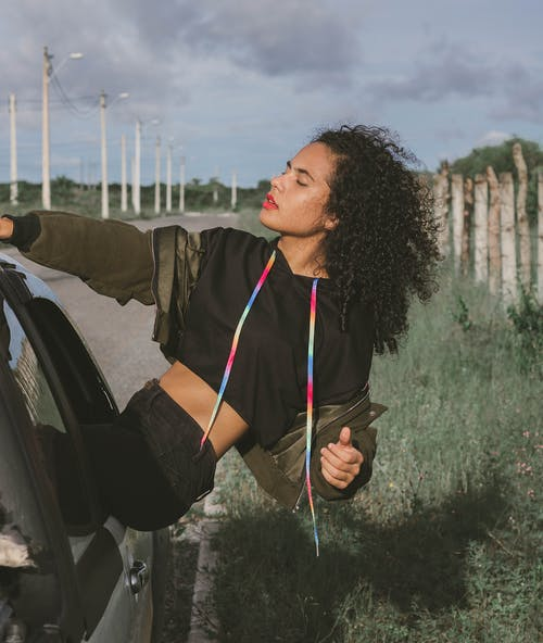 Calm young ethnic female with curly hairstyle and closed eyes enjoying fresh wind from opened car window