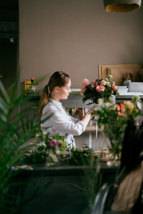 Woman with bouquet of flowers in floral shop