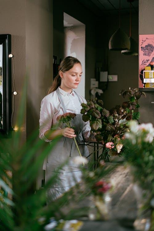Florist standing near green plants