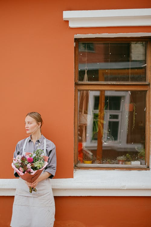 Calm female in apron standing with bouquet of flowers in wrapping paper standing at orange house with window on street