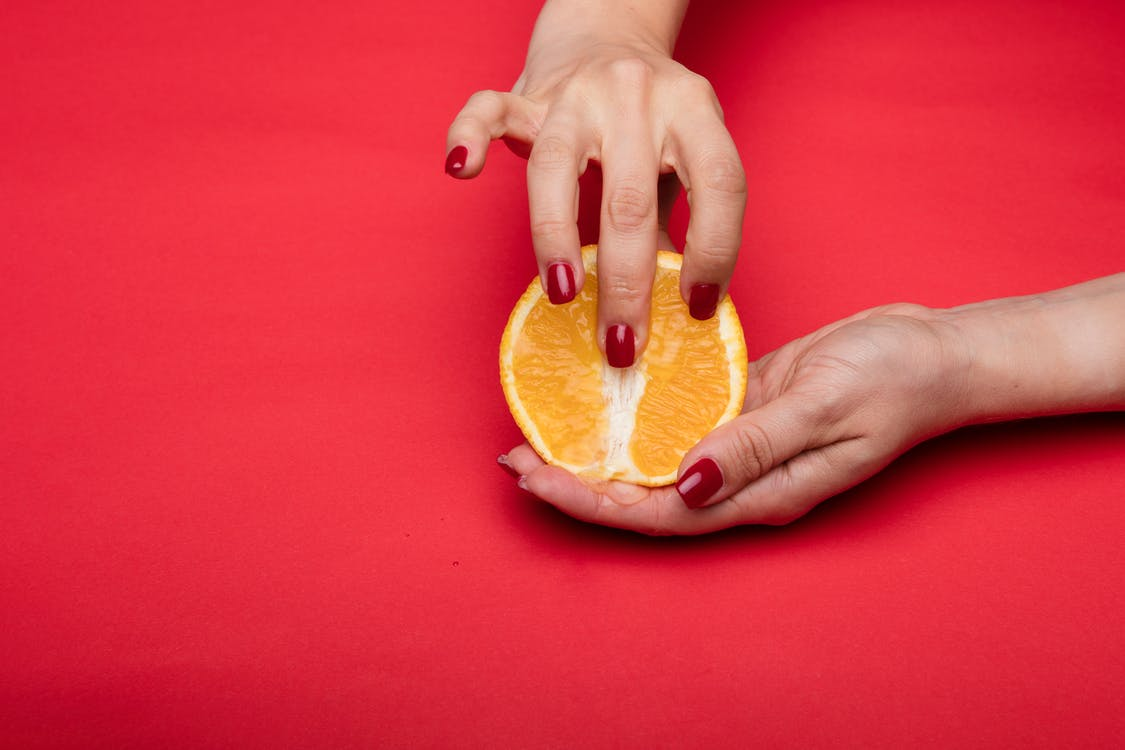 Person Holding Orange Fruit on Red Textile