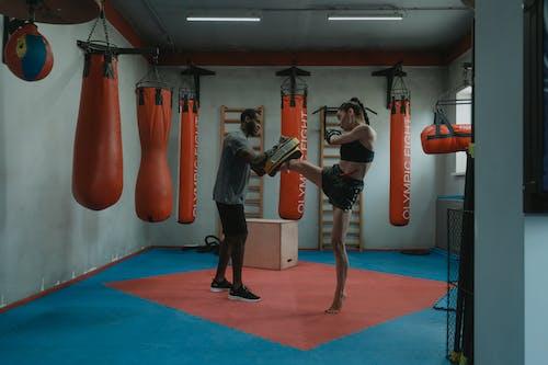 Woman Doing High Kick During Boxing Training