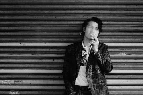 Black and white of young ethnic male in stylish clothes standing on street near weathered wall with hand in pocket and smoking cigarette
