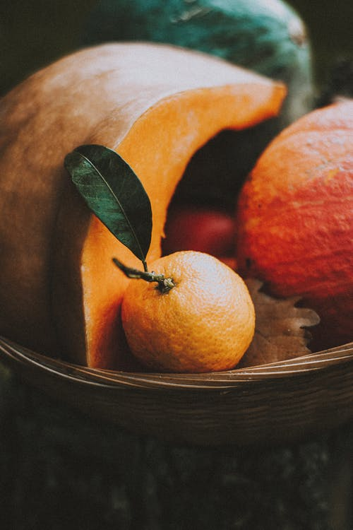 Colorful tangerine with leaf in wicker basket with cut pumpkin in soft light