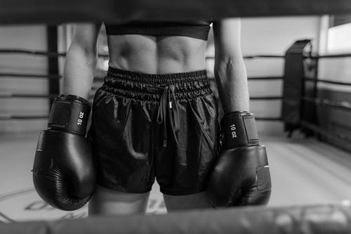 Grayscale Photo of Woman in Black Boxing Gloves