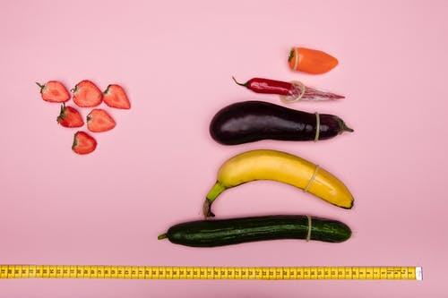 Measuring Vegetables and Fruits on Pink Surface
