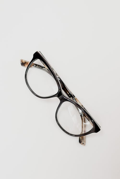 From above of glasses for correcting eyesight in trendy rim placed on white table