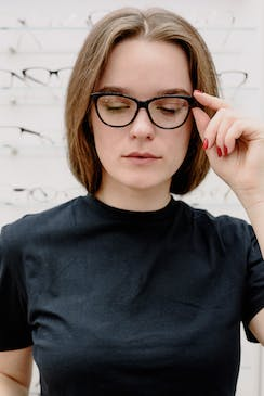 Woman being fit for dark frame glasses