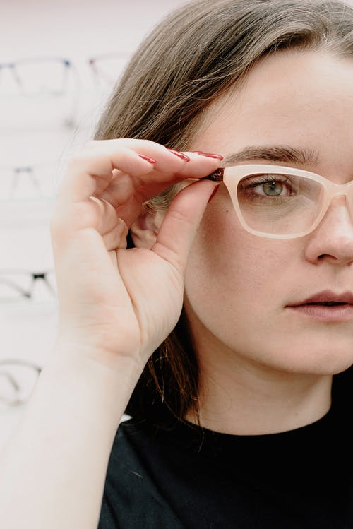 Crop young female client putting on eyewear while choosing new rim glasses in salon