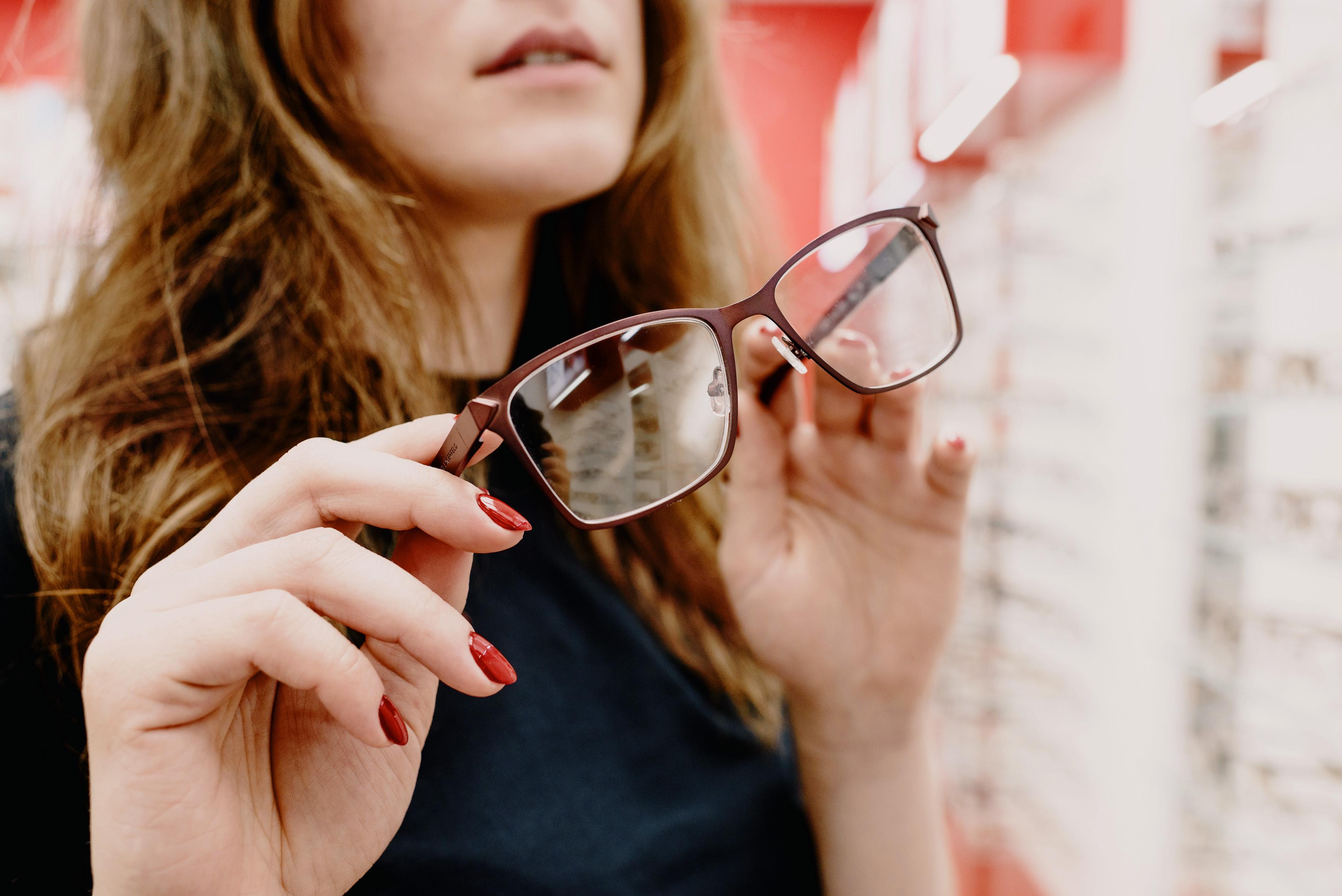 woman choosing glasses in eyewear store