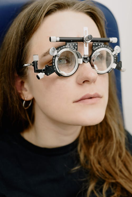 Young woman in glasses rim with lenses during check up