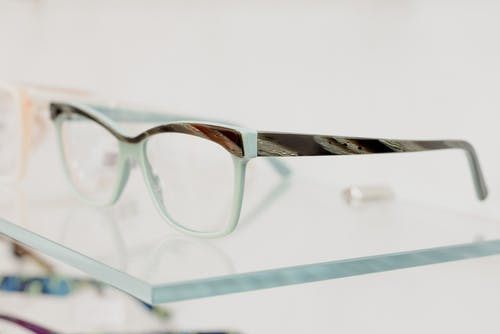 Modern glasses on transparent shelf in optical shop with various lenses and rims