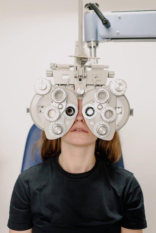 Woman checking eyesight with modern testing equipment