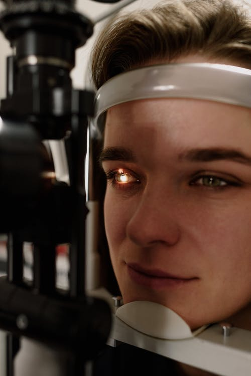 Headshot of concentrated female patient having eyesight examination with special optical equipment while sitting at professional slit lamp in clinic