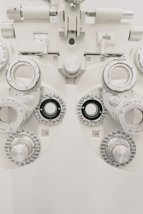 Contemporary medical equipment with ophthalmic glasses for examining vision made of steel placed on white background in modern light clinic