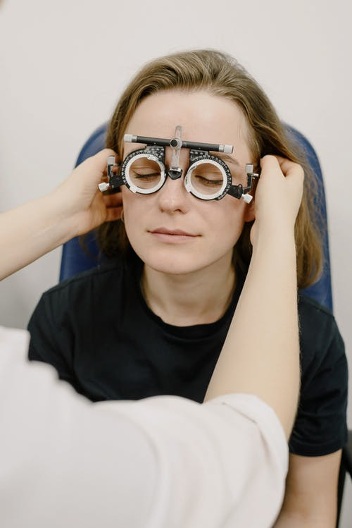 Unrecognizable medic adjusting phoropter with diopters on eyes of female patient while doing vision check up in clinic during appointment