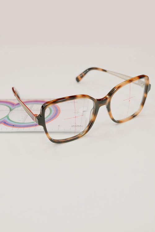 Modern eyeglasses with lens ruler on white background