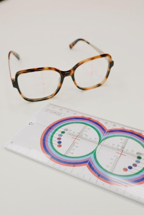 Professional lens ruler near modern eyeglasses on table