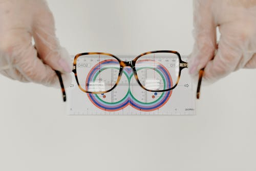 From above of crop anonymous oculist in sterile gloves measuring modern eyewear with optical tool on white background