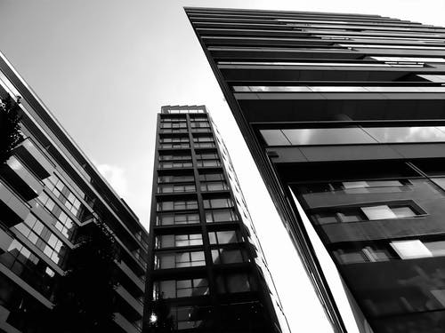 Grayscale and Low Angle Photography of High-rise Buildings