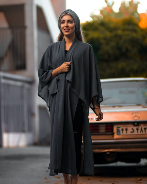 Woman in Gray Long Sleeve Dress Standing on Road