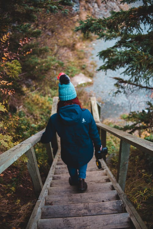 From above back view of unrecognizable redhead female traveler in warm clothes and hat walking down wooden stairs amidst autumn trees towards sea