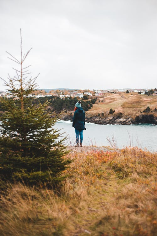 Back view of unrecognizable female traveler in warm outerwear and hat standing on grassy coast of waving sea and admiring picturesque landscape under cloudy sky