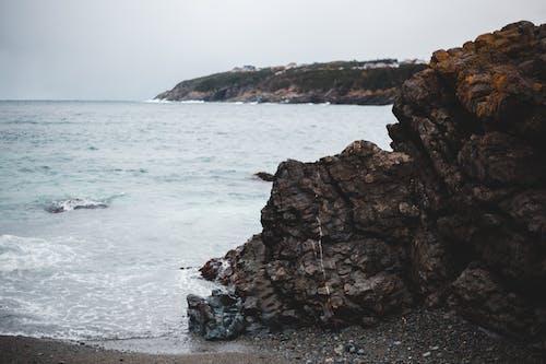 Waving ocean washing sandy shore near rocky formation under dramatic sky