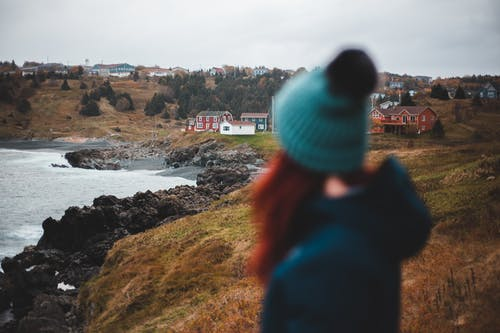 Back view of female in outerwear admiring cottages of countryside on coast covered with grass