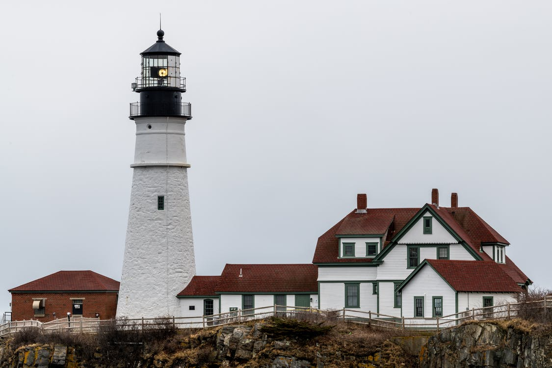 White lighthouse and aged residential houses against cloudy sky