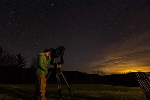 Side view of unrecognizable male traveler in warm clothes and hat observing starry night sky with telescope standing on grassy meadow in hilly terrain